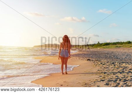 Lonely Young Woman Walking On The Beachsunset Day.beach Woman In Fashion Beachwear Relaxing Walking