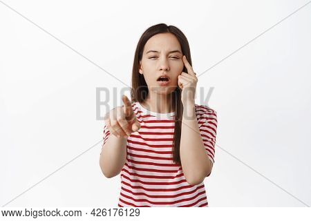 Image Of Young Woman Pointing Finger, Squinting Eyes Without Glasses, Cant See, Trying To Read Smth