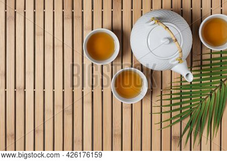 White Teapot And Tea Cups With Tea Drink Top View.  Asian Tea Ceremony.