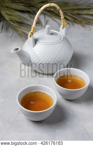 Asian Tea Ceremony. Teapot And Tea Cups With Tea Drink On Table.