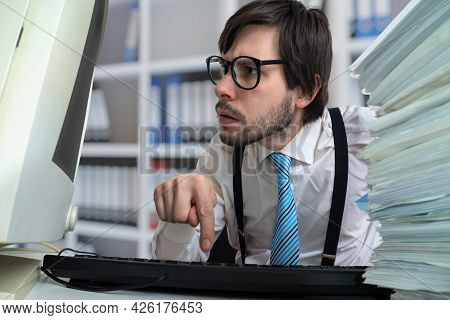 Young Man Is Working With Desktop Computer In Office.