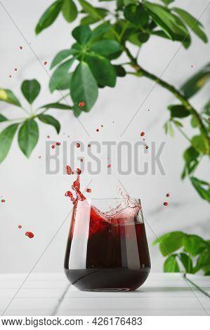 Cherry Juice In Glass. Juice Splash. Juice On Tile Table Summer Concept