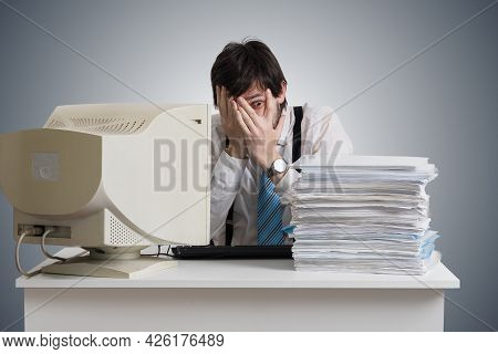 Funny Man Is Covering Face And Looking On Pile Of Documents On Desk. Paperwork Concept.
