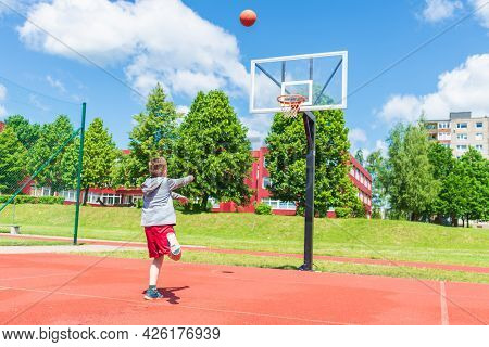 Attractive Young Boy Shooting Ball To The Hoop At Playground.cute Young Boy Plays Basketball On The