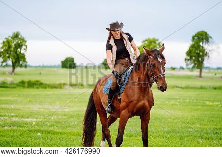 Young Woman Dressed In Riding Clothes And Hat Riding Brown Horse In Green Field