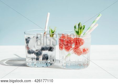 Two Glasses With Cool Lemonade, Water With Berries, Cocktail With Cocktail Tubes On A Pastel Backgro