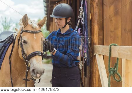Female Jockey With Her Light Brown Horse Outside The Stable. The Girl Is Dressed In A Blue Checked S