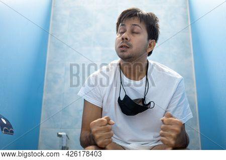 Young Asian Man Suffering From Stomachache Sitting On Toilet Bowl, Diarrhea, Stomach Disease