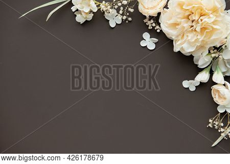 Light yellow peonies pattern on brown background