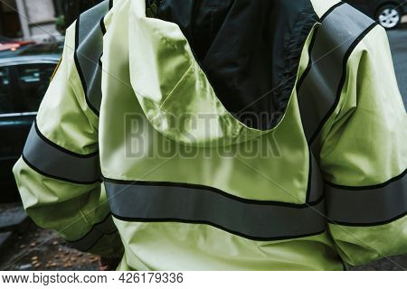 Rearview of a man in a high visibility jacket by the street