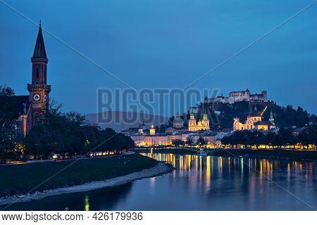 Salzburg city evening view. Cathedral, Old Town Altstadt, Evangelische Pfarrgemeinde Christuskirche Hohensalzburg castle illuminated at night. Salzach River waterfront promenade. Salzburg, Austria