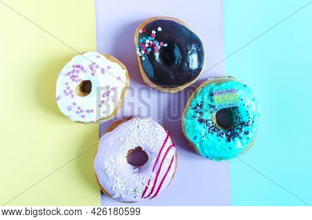 Fresh Donuts With Colored Glaze On A Colored Background. Multicolored Donuts On A Three-color Backgr