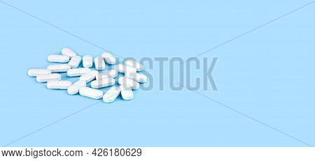 Banner. Close-up White Pills On The Blue Background. Medicine And Healthcare Concept. Place For Text