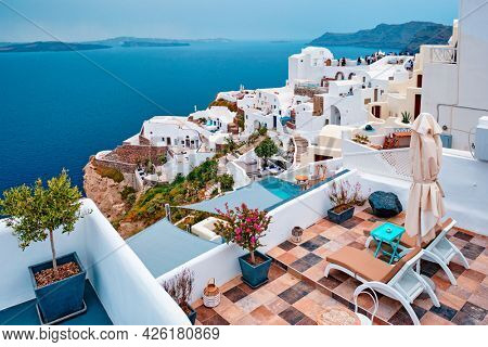 Famous greek iconic selfie spot tourist destination Oia village with traditional white houses and windmills in Santorini island, Greece