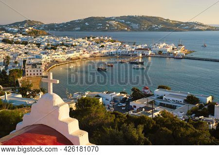 View of Mykonos town Greek tourist holiday vacation destination with famous windmills, and port with boats and yachts on sunset over St Basil church cross. Mykonos, Cyclades islands, Greece.
