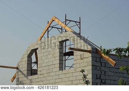 Attic Of A White Brick Unfinished House With Empty Windows Against The Background Of The Gray Sky