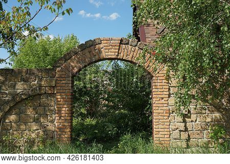 Empty Abandoned Old Brown Brick Gate And Fence Wall On The Street Overgrown With Green Grass And Veg