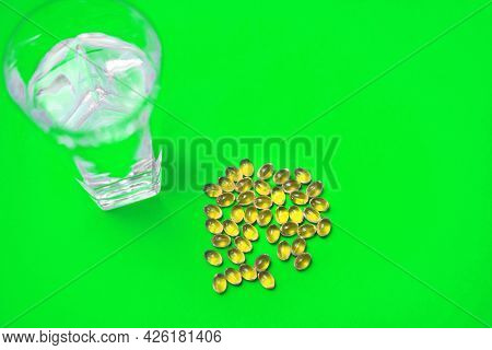 Fish Oil In Capsules And A Glass Of Water On A Green Background. The Concept Of A Food Supplement In