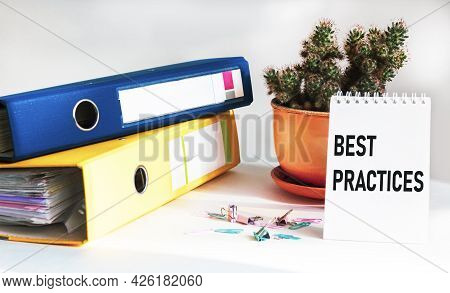 Business Term, Business Phrase. Text On Notebook - Best Practice. Folders, Paper Clips And Cactus On