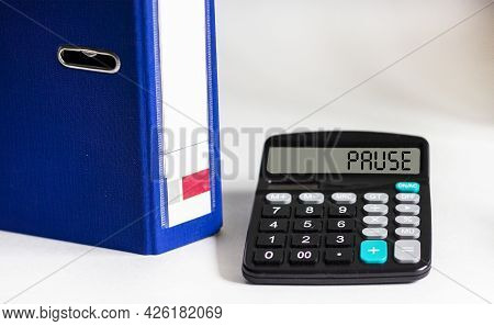 Calculator With Word Pause On Display Isolated On White Background With Blue Folder For Documents