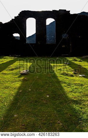 Spectacular Sun Behind Silhouetted Ruined Gothic Church, Throwing Light Onto Green Grass.