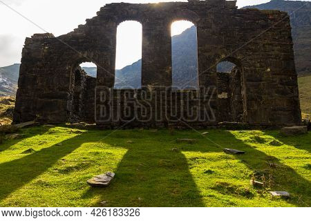 Spectacular Sun Behind Ruined Gothic Church, Throwing Light Onto Green Grass.