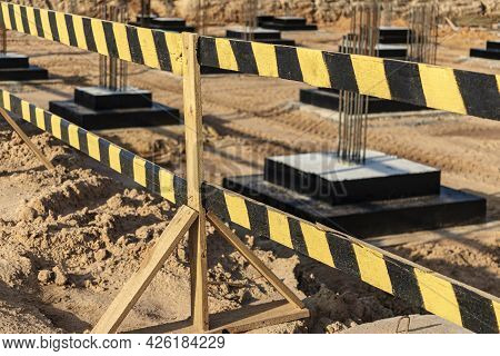 Construction Pit Fencing. Construction Safety. Construction Site With Reinforced Concrete Foundation