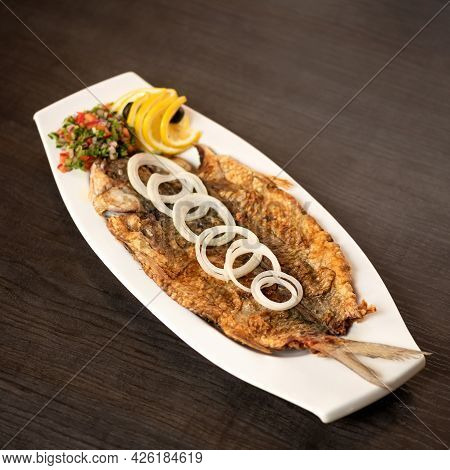 Platter With Fried Whole Fish On Wooden Table. Dish Decorated With Vegetables, Onion And Lemon Slice