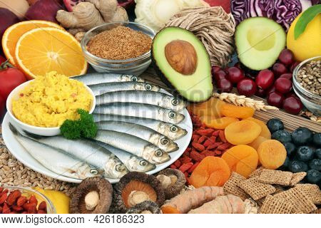 Healthy food for fitness and vitality concept high in antioxidants, protein, omega 3, vitamins,  anthocyanins and fibre. Seafood, vegetables, fruit, cereals, seeds, grains and supplement powders.