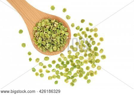 Roasted green peas health food in a wooden spoon and loose on white background. High in dietary fibre, protein, vitamins and minerals with many health benefits. Flat lay, top view, copy space.