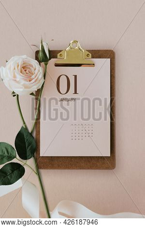Pastel pink calendar on a cork clipboard with light pink rose