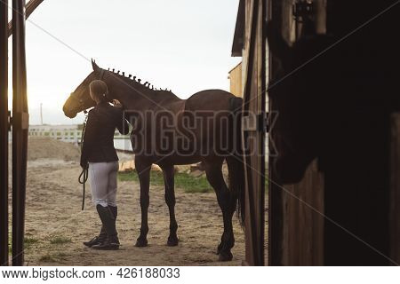 Back View Of A Horse Woman Standing With Her Dark Bay Horse Outside The Stable. Posing For The Camer
