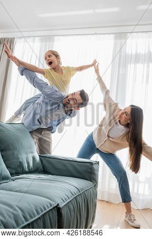 Cheerful Family Having Fun While Imitating Flying At Home