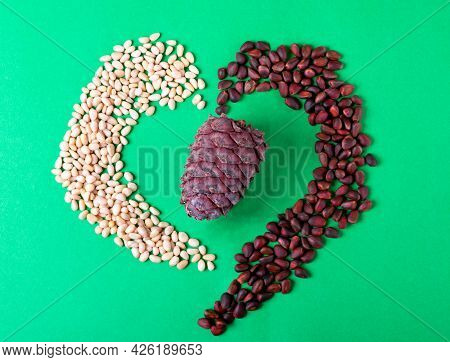 Shelled And Unshelled Pine Nuts Are Shaping The Heart Around The Cedar Cone On Green. Concept Of Ben