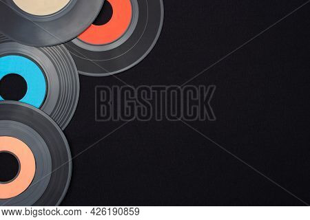 Multi Colored 7 Inch Single Vinyl Records On A Black Background Placed On Top Left Corner With Empty