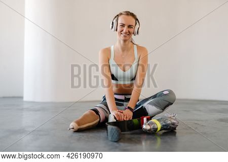 Disabled happy young white sportswoman in headphones with prosthetic leg sitting on a floor in room