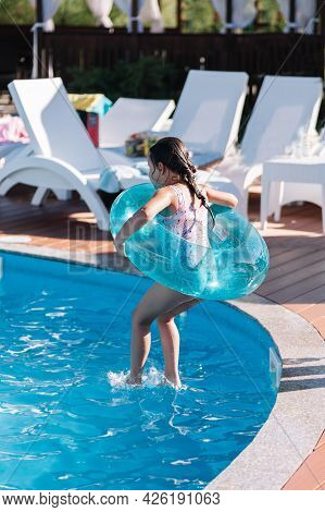 The Child Has Fun Jumping Into The Water From The Side Of The Pool And Holding A Transparent Blue In