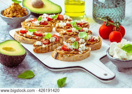 Bruschetta or open ciabatta sandwiches with avocado and tomato spread and feta cheese