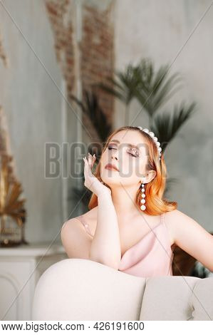 Portrait Of A Red-haired Young Woman With Closed Eyes In A Silk Dress With Pearl Makeup And Pearl Ac