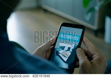a young man, sitting at home, is using a password manager in his smartphone, with a mock password manager app in its screen
