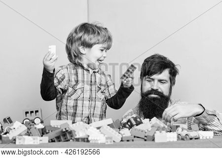 Bearded Hipster And Boy Play Together. Dad And Child Build Plastic Blocks. Child Care Concept. Happy
