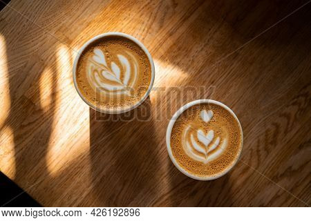 Two Cups Of Fresh Coffee With Latte Art On Wooden Table In Sunlight. Morning Cappuccino With Hearts