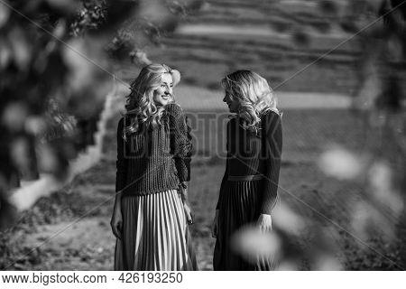 Femininity And Tenderness. Women Walking In Autumn Park. Pleated Skirt Fashion Trend. Friends Girls.