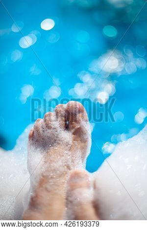 Womens Feet And Fingers In Foam At A Foam Pool Party, Relaxation And Spa On Summer Vacation