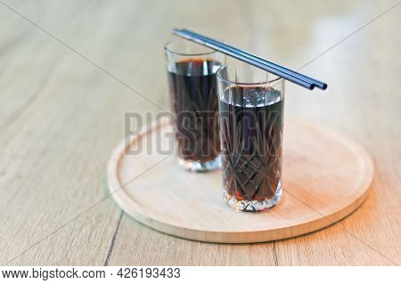 Two Glasses Cuba Libre Or Long Island Iced Tea Cocktail With A Cola, Rum With Straws On Wooden Table