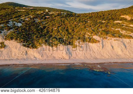 Aerial View Of Summer Coastline With Cliff, Trees And Quiet Sea. Coastline With Sunset Colors