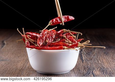 Chopsticks With A Pod Of Hot Red Pepper Over A Bowl Of Pods.