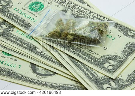 Close-up Cannabis In Small Plastic Bag Against Two Dollars Banknotes Background. Therapeutic And Med