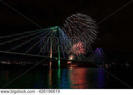 Bright Flashes Of Fireworks In The Night Sky Above The Illuminated Bridge In Krasnoyarsk, Russia