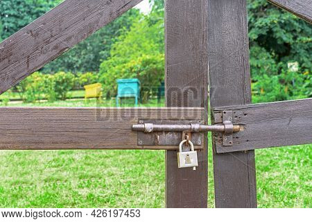 Old Metal Latch With A Lock On The Wooden Gates Of The Honey Apiary.